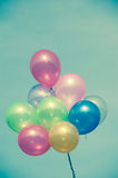 Multicolored balloons. On blue sky ; vintage color tone royalty free stock photography