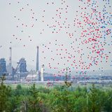 Multicolored balloons in the sky against the background of the pipes of a large metallurgical plant. Contrasts of nature, industry. And the results of human stock images