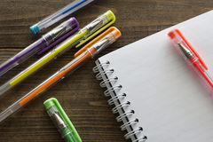 Multicolored ballpoint pens and notebook stock image