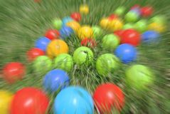 Multicolored balls - children's toys, on green grass, with radial blur Royalty Free Stock Photos