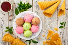 Multicolored balls of cream ice cream on an ice plate. Multicolored balls of cream ice cream on an ice plate, tea and waffle cones on a wooden table Royalty Free Stock Photo