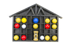 Multicolored balls and sand clock in wooden shelf stock image