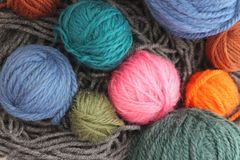 Multicolored balls of woolen yarn on grey thread background. Multicolored pink, blue, green, orange, brown balls of woolen yarn on grey thread background. Hobby Royalty Free Stock Image