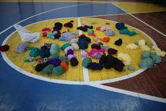 Multicolored balls of yarn on the basketball field. Many multicolored balls of yarn on the basketball field Royalty Free Stock Photos