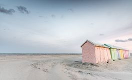 Multicolored beach bathing cabins. Multicolored bathing cabins lined up on the deserted beach of Berck in the early morning Stock Images