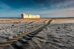 Colorful beach bathing cabins. Multicolored bathing wooden huts lined up on the deserted beach of Berck-sur-Mer, France, in the early morning Royalty Free Stock Photos