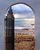 Multicolored Beach Gate in Vieques, Puerto Rico Leading To Sunset Beach With Cloudy Skies. Concrete and wrought iron entryway to the beach, showing a storm stock photography
