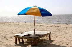 Multicolored Beach Umbrella in wooden stand on beach. Stock Images