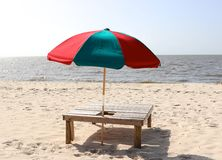 Multicolored Beach Umbrella in wooden stand on beach. Red and Green beach umbrella in a wooden bench on Biloxi beach Royalty Free Stock Photos