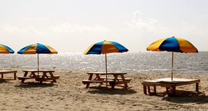 Multicolored Beach Umbrellas in wooden stand on beach. Blue and Yellow beach umbrellas in wooden benches line the beach in Biloxi, Mississippi Stock Photography