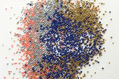 Multicolored beads in glass jars. Beads are poured on a white background. Plastic multi-colored polymers. Plastic pillets stock photo