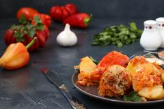 Stuffed peppers with meat, rice and tomato sauce. Located in a plate on a dark background. Multicolored bell pepper stuffed with meat, rice and tomato sauce Royalty Free Stock Images