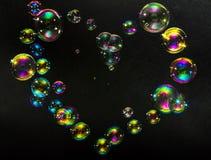 Multicolored bellen in de vorm van harten op een donkere achtergrond Stock Foto's