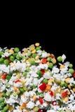 Multicolored bevroren groenten bij de bodem van het kader op een zwarte achtergrond Stock Foto's