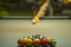 A multicolored billiard balls lie in the shape of a triangular pyramid on the blue cloth of the table against the background of a stock image