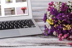 Multicolored bloemen en laptop op witte houten lijst royalty-vrije stock afbeelding