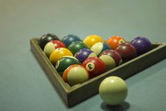 Amulticolored blurred billiard balls with numbers lie in a wooden triangle pyramid on the blue cloth of the table stock photo