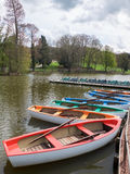 Multicolored boats and pedal boats on a pond. Stock Images