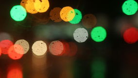 Multicolored bokeh from street and traffic lights at night. Car wiper works, raininng stock video