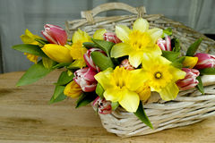 Multicolored bouquet spring flowers with wicker basket on wooden Stock Image
