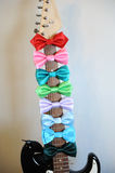 Multicolored bow ties on a guitar fretboard neck. White background, free space for text. Multicolored bow ties on guitar fretboard neck. White background, free Stock Photos