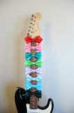 Multicolored bow ties on a guitar fretboard neck. White background, free space for text Royalty Free Stock Photos