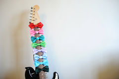 Multicolored bow ties on a guitar fretboard neck. White background, free space for text. Multicolored bow ties on guitar fretboard neck. White background, free Stock Images