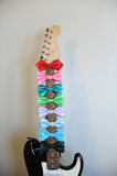 Multicolored bow ties on a guitar fretboard neck. White background, free space for text Stock Photos
