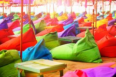 Multicolored bright beach umbrellas, ottomans and tables in the beach cafe. Summer multicolored background Royalty Free Stock Images