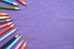 Multicolored, bright, colorful pencils for drawing on the lef. T by an arc and a place for your text on a background of purple cloth Stock Photos