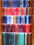 Multicolored bright male ties on hanger in a store stock images