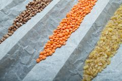 Multicolored and bright organic cereals: lentils, bulgur and buckwheat on parchment paper. The concept of a healthy diet, royalty free stock photos