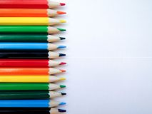 Multicolored bright pencils of the same size lie flat on white paper, separated by the colors of the rainbow stock image