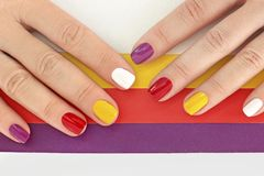 Multicolored bright saturated manicure on short nails close-up. stock photography