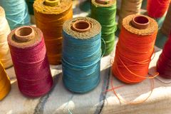 Multicolored bright spools of thread close-up on a blurred background of other spools royalty free stock image