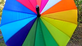 Multicolored bright umbrella spin around closeup. Slow motion stock video footage