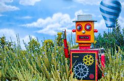 Multicolored bright wooden toy robot on green floral background with blue ballon and sky behind stock photography
