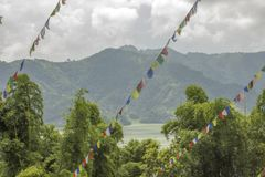 A multicolored Buddhist Tibetan prayer flags against the green forest of a lake and mountains stock image
