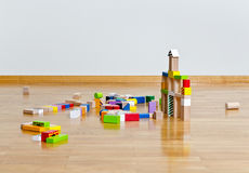 Multicolored building blocks. On wooden floor against white wall Stock Photo