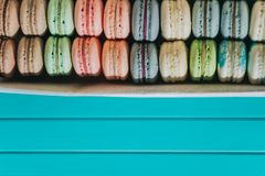 Multicolored cake macaron or macaroon or almond cookies lie in a box on a turquoise background, pastel colors, copy. Space Royalty Free Stock Photos
