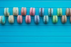 Multicolored cake macaron or macaroons lie on a wooden turquoise background, top view, copy space. Multicolored cake macaron or macaroons lie on a wooden Royalty Free Stock Photo
