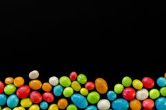 Multicolored candy on black background with space for text.  royalty free stock photo