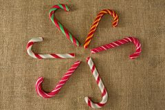 Multicolored candy canes arranged on fabric Royalty Free Stock Photos