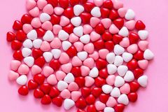 Multicolored candy or Pills in the shape of hearts. Concept Valentine`s Day or Medicine, Pharmacy, Cardiology. Pink background. Multicolored candy or Pills in royalty free stock images