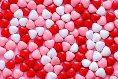 Multicolored candy or Pills in the shape of hearts. Concept Valentine`s Day or Medicine, Pharmacy, Cardiology. Pink background. Multicolored candy or Pills in stock photo