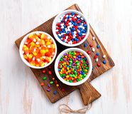 Multicolored candy sunflower seeds in the icing sugar and corn for Halloween. Stock Photography