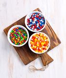 Multicolored candy sunflower seeds in the icing sugar and corn for Halloween. Royalty Free Stock Photo