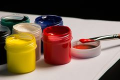 Multicolored cans of gouache with Paintbrush royalty free stock photos