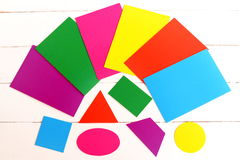 Multicolored cardboard geometric shapes. Cut from color cardboard triangle, square, oval, trapezoid, rectangle, circle Stock Photos