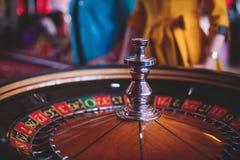 Multicolored casinolijst met roulette in motie met groep gokkende rijke rijke mensen op de achtergrond Stock Afbeelding